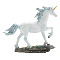This glorious creature will grace your table or shelf, bringing elegance and a hint of magic to your home. This beautiful white unicorn has a shimmering blue mane with a golden horn, and walks among rocks with blooming flowers.